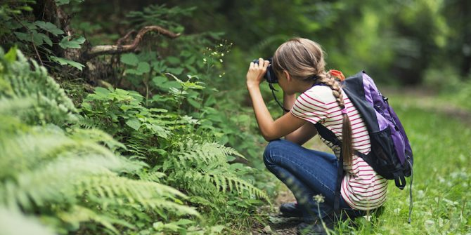 A person is crouching along a trail in the forest, taking a photo of wildlife.
