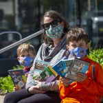 A family of three sit outside of the library in the summertime. All have masks on and are showing off their borrowed items.