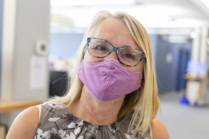 A library staff person is wearing mask but you can tell by her eyes she has a big smile.