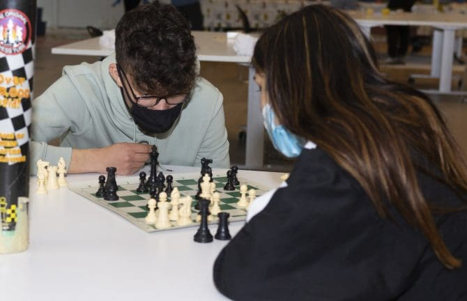 Two teens are being safe by wearing masks while engaged in a chess match.