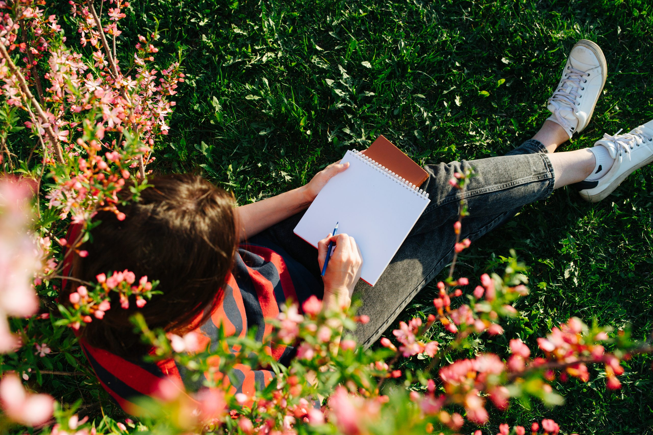 Girl sitting on grass in a flowered garden with a notepad and pen in her hands.