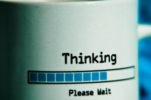 "A mug with the inscription ""Thinking ... Please Wait""."