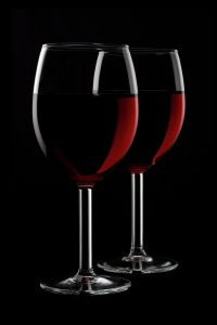 Image is of two glasses of red wine with a dark background