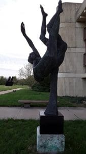 image is of a sclupture representing Icarus, the mythlogical being and a more modern angular and linear sculpture in the background