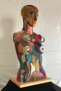 Image is of a colorful bead covered woman's head and torso