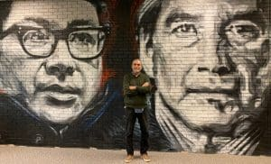 Image is of Dr. Daniel Wildcat standing in front of portraits of Dr. Wildcat & Vine Deloria Jr. by Steven Grounds