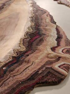 Image is of a close up photo of colorful beaded detail on a tree cutting with wavy wood grains