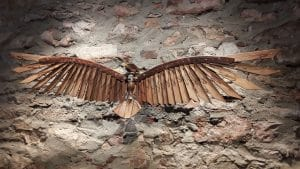Image is of a large bird created from used furniture pieces that is hanging on a rustic stone and brick wall
