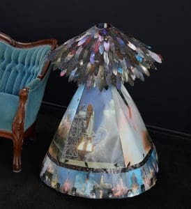 Image is of an elaborately decorated dress in vivid blues; the skirt is covered in images of space flight and crows, and a shawl of multicolored feathers