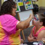 A woman paints a child's face
