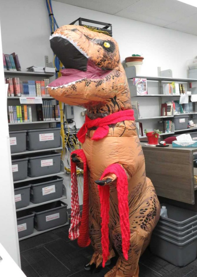 An inflatable Tyrannosaurus rex collects red scarves
