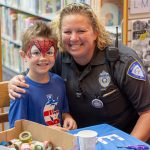 A police officer puts her arm around a child with Spider-Man face paint