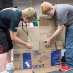 Teens building a cardboard structure
