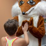 Library mascot Booker high fives a child