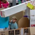 A child builds with cardboard boxes