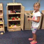 A child uses the play kitchen