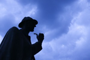 silhouette of person wearing a deerstalker cap and holding a pipe