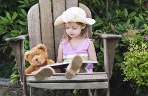 girl reading to teddy bear
