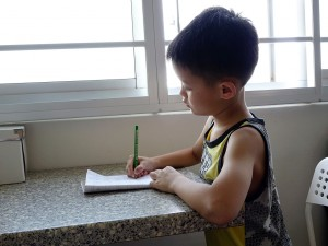 boy sitting at a table writing
