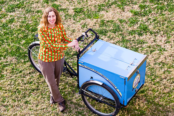Librarian Karen Greene standing with Bookbike