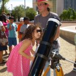 girl looks into large telescope