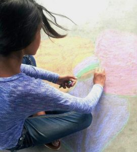 Youth chalking outside Woods Memorial Library.