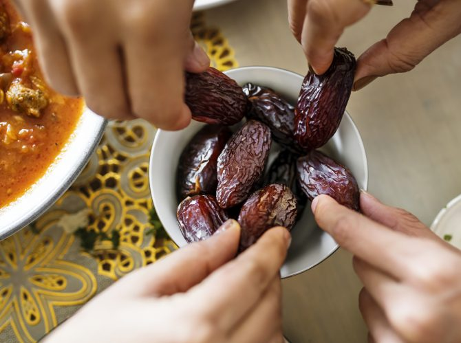 bowl of dates with hands reaching and grabbing fruit