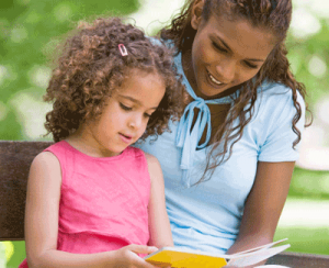 Mother and daughter reading outside