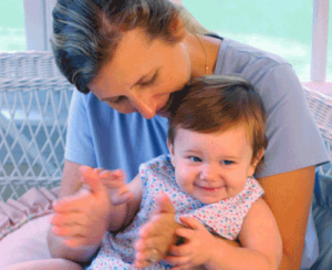 Mother singing to child sitting on her lap and clapping hands