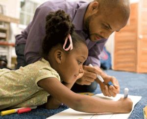 Dad helping his daughter writing