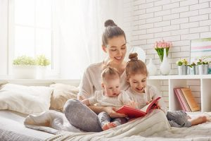Mother reading with baby and toddler in bed