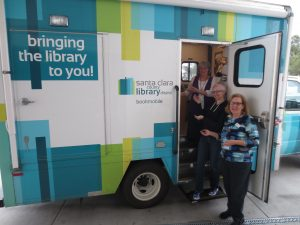 Welcome to the Bookmobile. Side view with open door and Bookmobile team.