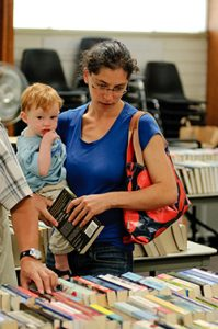 Woman with baby looking at donated books.