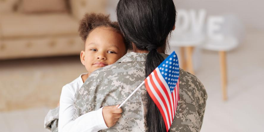 Lovely charming pretty girl hugging her mom tightly while greeting her home and holding a flag in her hand