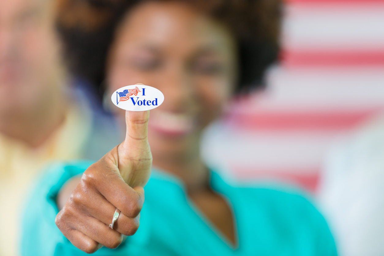 """African American Woman with an """"I Voted"""" sticker"""