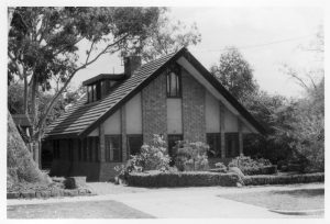 Ivanhoe. Walter Burley Griffin House. 21 Glenard Drive. Shows front exterior view of two storey brick residence with sloping roof. Source: J.T. Collins Collection, La Trobe Picture Collection, State Library of Victoria.