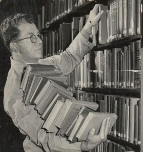 Man in dust coat replacing armful of books onto shelves. Source: State Library Victoria via The Age