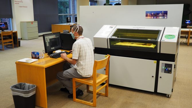 Photo of a staff member using the computer software to activate the UV printer