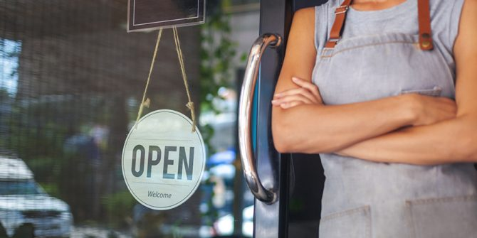 Woman stands next to open sign in doorway, small business reference center