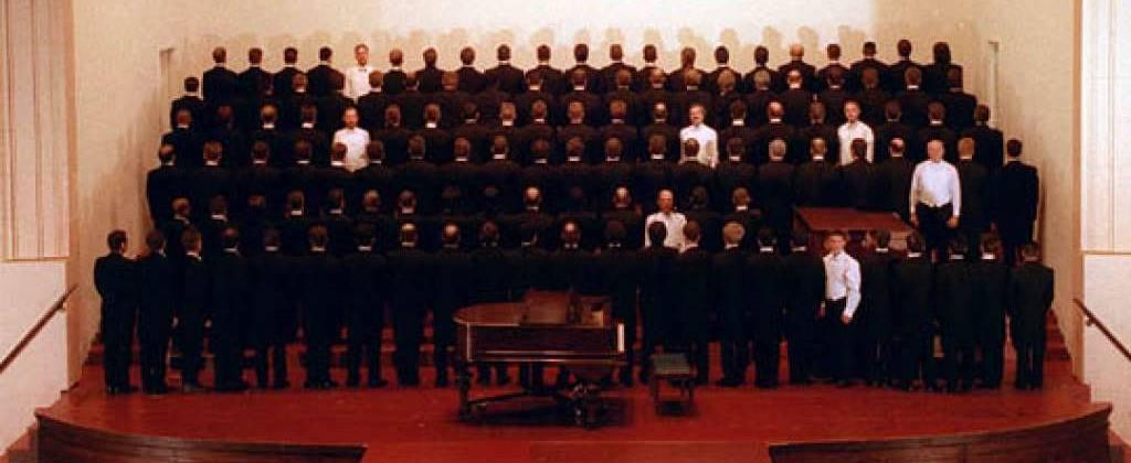San Francisco Gay Men's Chorus members are standing in 6 rows. 7 of them are dressed in white and facing the camera, the rest are wearing usual black concert tuxedo and have their backs to the camera.
