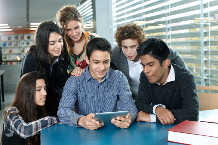Group of teenagers looking at a digital tablet